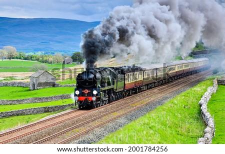 The locomotive smokes and rushes along the railway. Train ride on railroad. Locomotive smoke Photo stock ©