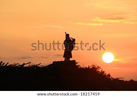 The lone bagpiper at sunset, on a hill