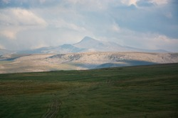 The lone protruding peak of mount Sartsali seen across meadows and bare hillsides of the south of Armenia