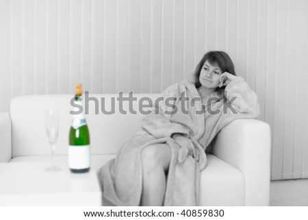 The lonely young woman sits on a sofa and looks at a wine bottle