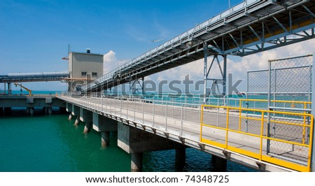 The long jetty reach to the sea to supporting the tanker marine ship loading the lignite charcoal coal oil and fuel