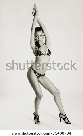 The long-legged beauty poses on a light background - stock photo