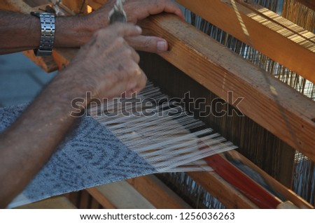 The loom for work with flax. Manufacture of linen cloth in manual. Flax. A man makes a billet cloth on a loom #1256036263
