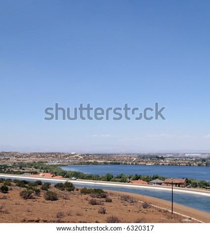 The Los Angeles aqueduct runs through the city of Palmdale in southern California. Luxury homes between the aqueduct and Palmdale lake in the background.