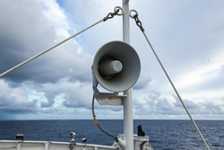 The loudspeaker is attached to the mast of a ship at sea.