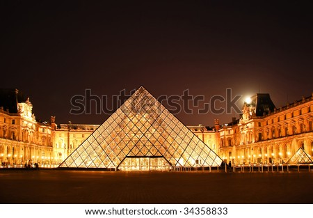 The Louvre and the Pyramide in Paris, France at night