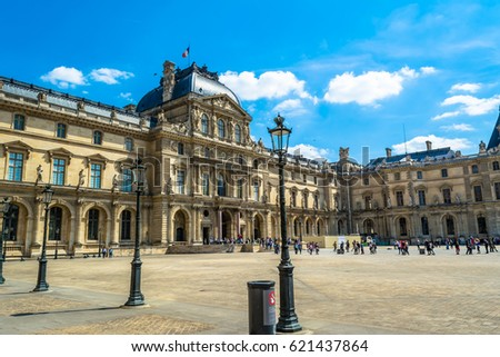 The Louvre in Paris on a sunny day with blue sky.