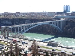 The lovely and lively Niagara Falls with clean, blue water flowing down the river under the bridge connecting ontario to buffalo city, usa, with vehicles on the road travelling for fun or for work.