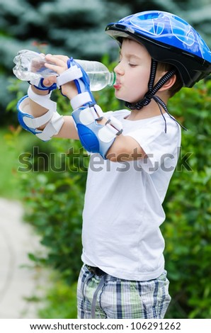 the lovely boy skater drinking water from a bottle