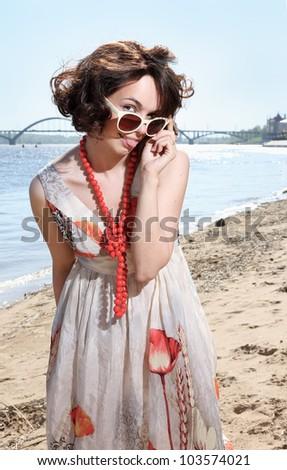 The lovely girl looks over sun glasses