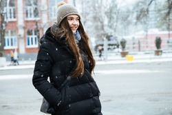 the lovely long-haired girl in a warm black jacket and hat walks through the winter city, smiling