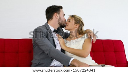 The lovers give flowers to the bride and kissed happy and couple love standing in wedding studio