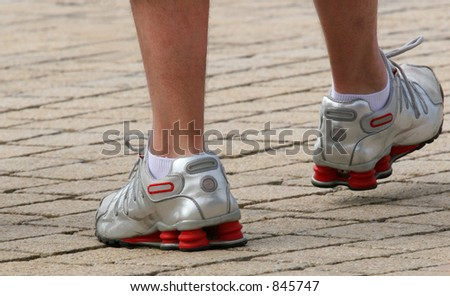 The lower legs of a man wearing silver and red trainers.