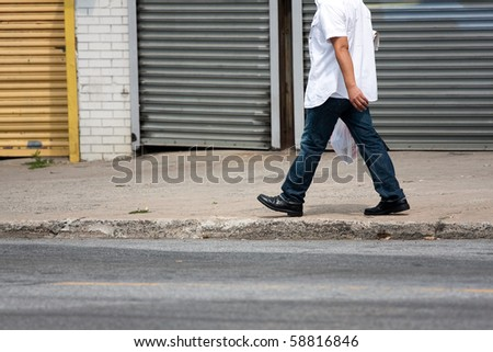 The lower torso of a man walking down the sidewalk along the side of the road.