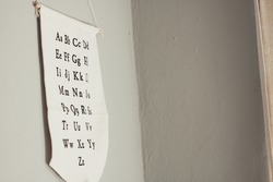 The lowercase and uppercase pairs of English alphabet letters on a white material suspended from a wall