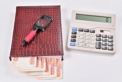 The lucrative business partners: money, calculator, magnifier  Office supplies and .