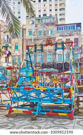 The luna park with different vintage swings in bright colors is located in residential neighborhood next to the Corniche avenue, Alexandria, Egypt #1009812190