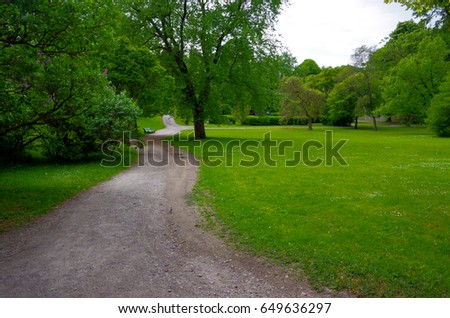 The lush park and the long pathway between the trees. - Shutterstock ID 649636297