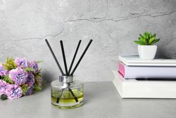 The luxury aromatic reed diffuser clear crystal glass display on the grey working table during work from home period