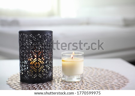 Photo of  the luxury black metal candle holder is displayed on the grey table with the lighting aroma scent candle in the white bedroom near sunlight from the curtain window