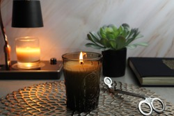 The luxury lighting aroma scented amber color glass candles is displayed with the candle warmer lamp on the grey table background of marble wall in the bedroom at night