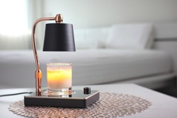 The luxury lighting aromatic scent  glass candle is put on the electric lamp candle warmer heater on the grey table in the white bedroom