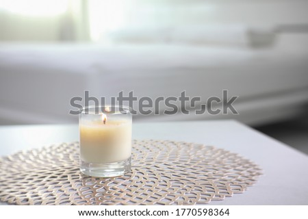 the luxury lighting aromatic scented glass candle display on the grey table in the white bedroom near sunlight from the curtain window