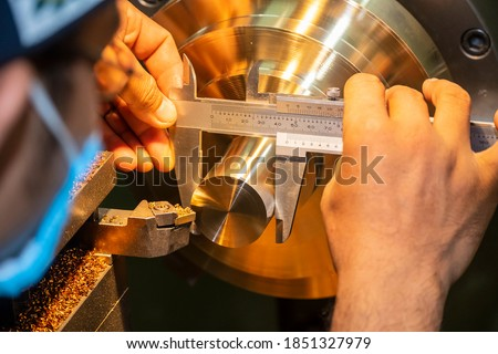 The machine operator measure the dimension of brass shaft by Vernier caliper. The quality control process of hi-precision parts manufacturing process. Photo stock ©