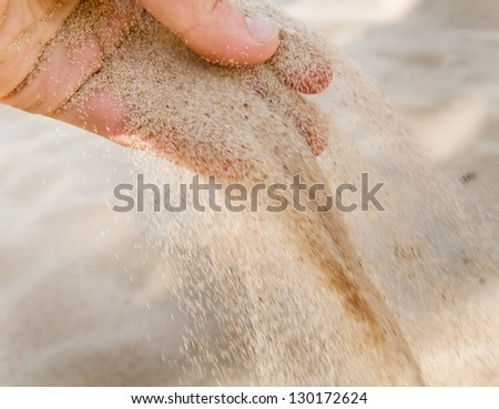 The macro snapshot of hand with sand strewed to fingers.