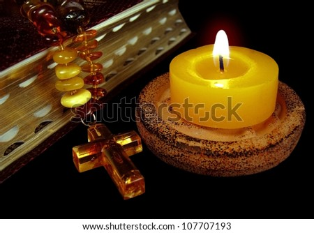 The macro - the bible photo with a gold sawn-off shotgun and an amber necklace with a cross and a burning candle