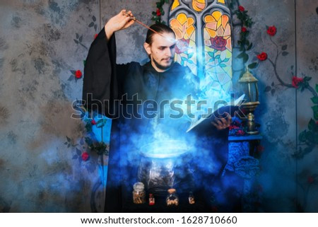 The mage is cooking a potion. A male wizard in a black mantle with a magic wand and a book. He casts a spell over the witch's cauldron. Guy in an old castle with luminous magic Сток-фото ©