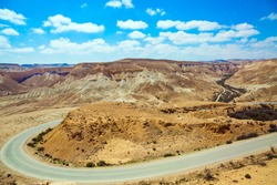 The magnificent gorge Ein Avdat is the most beautiful in the Negev desert. Aerial view. Serpentine highway glistens in the sun. Israel. The concept of environmental and photo tourism