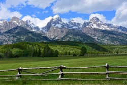 the magnificent peaks of the grand teton mountain range with a split rail fence in a pasture on a sunny day in grand teton national park, wyoming