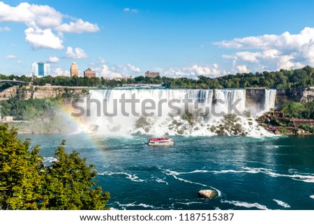 The Maid of the Mist in front of the American part of the Niagara Falls. Followed by a rainbow on the left side of the picture.