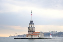 The maiden's tower (kız kulesi) in İstanbul, Turkey during overcast weather with sunshine reflection in bosporus sea.  Groups of seagulls flying on sea. İstanbul Turkey 01.03.2021