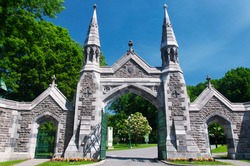 The main entrance and gate to the mount royal cemetery in montreal canada on a sunny blue sky day.