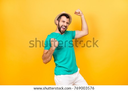 The main task is completed! Yeah! I did it! I reached so long desired success! Happy excited cheerful joyous guy celebrating his victory with raised hands, isolated on yellow background