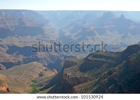 The majestic Grand Canyon of Arizona with arid rock formations and a river oasis running through it