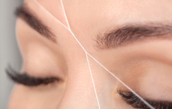 The make-up artist plucks eyebrows with a thread close-up. Women's cosmetology in the beauty salon.