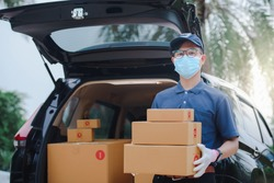 The male Asian delivery staff held a customer's paper box or box. The background is a freight car and has a box in the car The delivery workers wear protective masks and protective gloves.