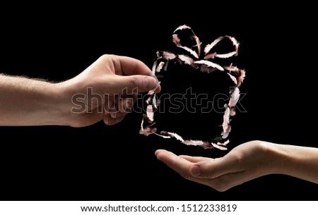 The male hand gives the woman the gift box be made of bird feathers on black isolated background. Concept of gifts giving.