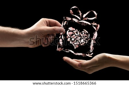 The male hand gives the woman the gift box be made of bird feathers with heart inside. On black isolated background. Concept of gifts giving.