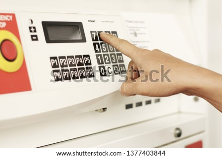 The male hand that is using the finger to press the button Numeric keypad, oil dispenser #1377403844