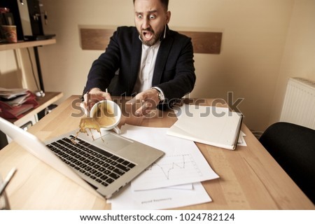 The male hands and coffee in white cup spilling in slow motion or movement on the table with laptop and documentation in the morning working day. The danger, security, safety, safeness, protection