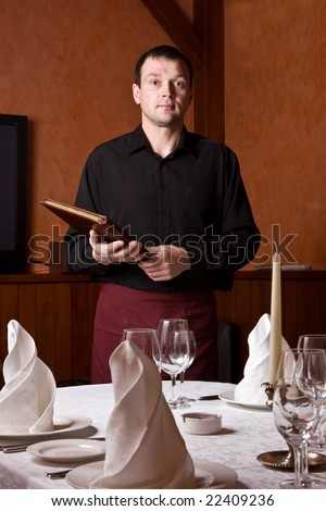 The male the waiter from the menu in hands at restaurant at a table