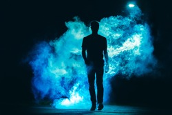 The male walking in the blue smoke on the dark background. evening night time