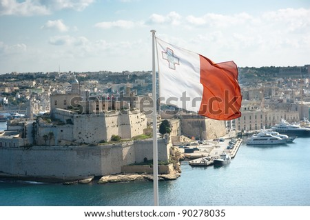 the maltese flag is flying from upper Barrakka gardens in Valletta and on the background the fortifications of Cottonera - stock photo