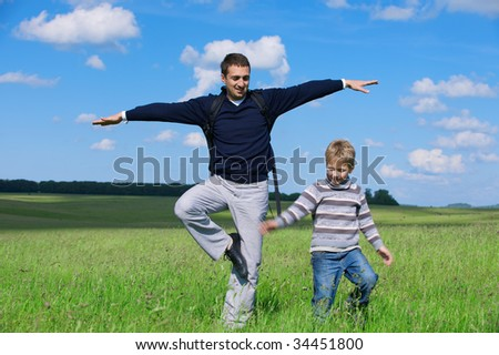 The man and the boy against the nature stand on one foot trying to keep balance