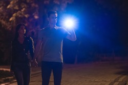 The man and woman stand with a flashlight on the dark street. night time