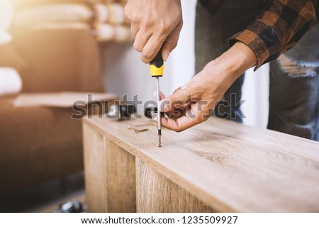 The man assembling new furniture at his home. #1235509927